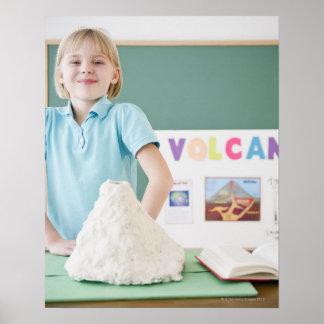 Caucasian girl standing with model volcano poster