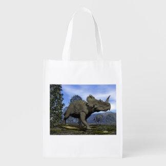 Centrosaurus dinosaurs walking among magnolia tree reusable grocery bag