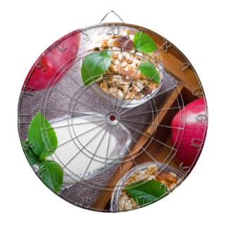 Cereal with walnuts and raisins, yogurt and apples dartboards