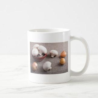 Champignon mushrooms and onions on the table coffee mug