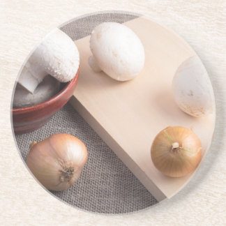 Champignon mushrooms and onions on the table drink coaster