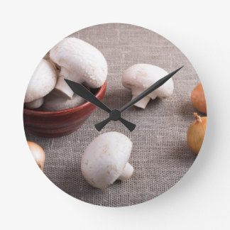 Champignon mushrooms and onions on the table round clock