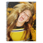 Cheerleader flipping hair, laughing, surrounded notebooks
