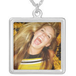 Cheerleader flipping hair, laughing, surrounded square pendant necklace