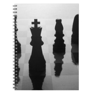 Chess pieces on chess board in black and white spiral notebook