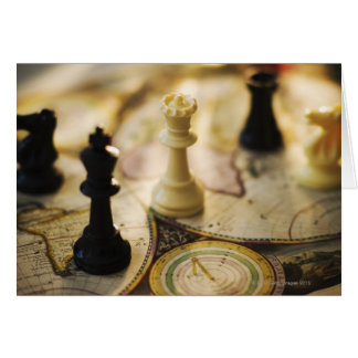 Chess pieces on old world map card