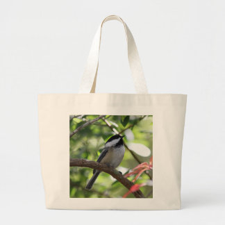 Chickadee perched in the forest large tote bag
