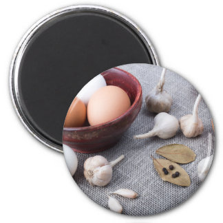 Chicken eggs and garlic and spices on the kitchen 2 inch round magnet