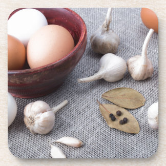 Chicken eggs and garlic and spices on the kitchen beverage coasters