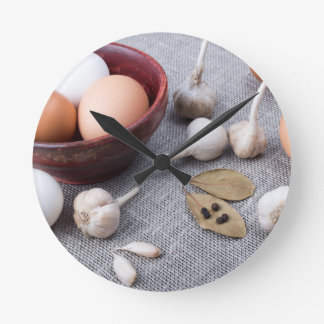 Chicken eggs and garlic and spices on the kitchen round clock