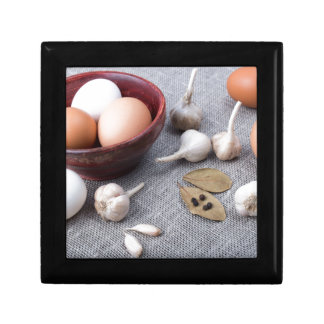 Chicken eggs and garlic and spices on the kitchen trinket box