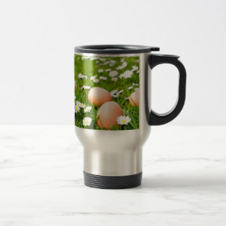Chicken eggs in grass with daisies travel mug