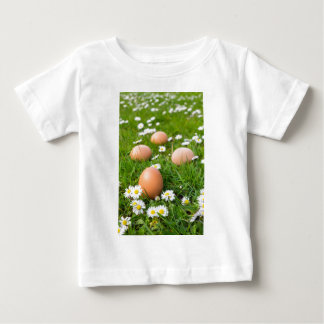 Chicken eggs in spring grass with daisies baby T-Shirt