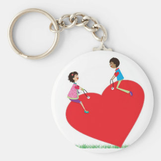 children playing on a heart shaped see-saw basic round button keychain