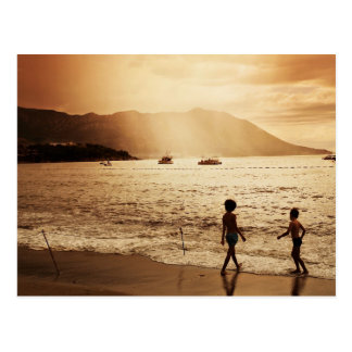 Children playing on the beach in sepia tones postcard