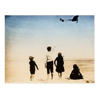 Children watching airplane on the beach postcard
