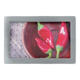 Chilli hot red pepper in a brown wooden bowl belt buckles