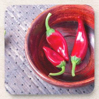 Chilli hot red pepper in a brown wooden bowl coaster