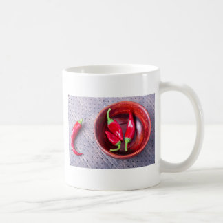 Chilli hot red pepper in a brown wooden bowl coffee mug