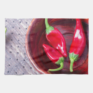 Chilli hot red pepper in a brown wooden bowl kitchen towel