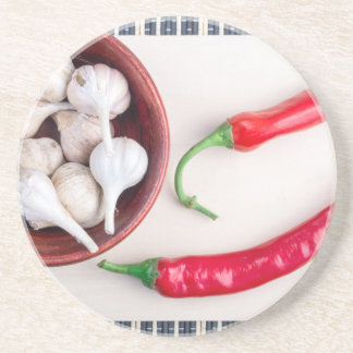 Chilli peppers and garlic in a wooden bowl coaster