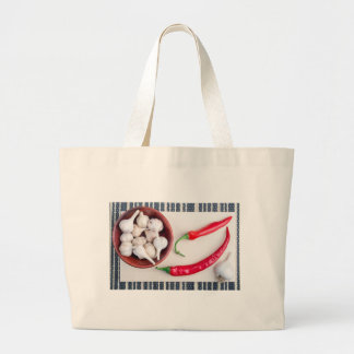 Chilli peppers and garlic in a wooden bowl large tote bag