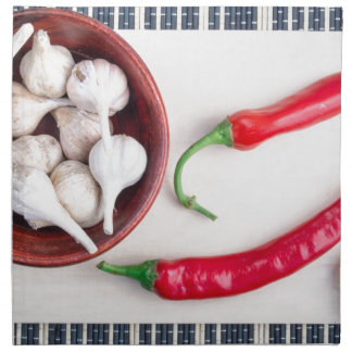 Chilli peppers and garlic in a wooden bowl napkin