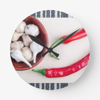 Chilli peppers and garlic in a wooden bowl round clock