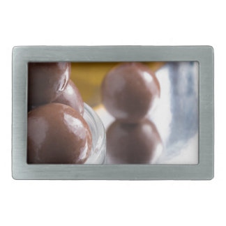 Chocolate candies in a small glass bowl close-up belt buckles