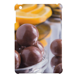 Chocolate candies in a small glass bowl close-up case for the iPad mini