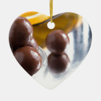 Chocolate candies in a small glass bowl close-up ceramic heart ornament