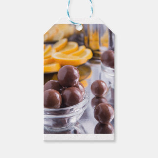 Chocolate candies in a small glass bowl close-up gift tags