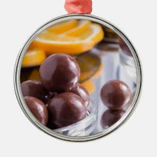 Chocolate candies in a small glass bowl close-up metal ornament
