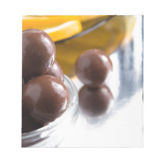 Chocolate candies in a small glass bowl close-up notepad