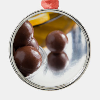 Chocolate candies in a small glass bowl close-up Silver-Colored round ornament