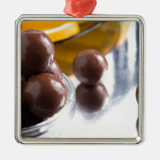 Chocolate candies in a small glass bowl close-up Silver-Colored square ornament