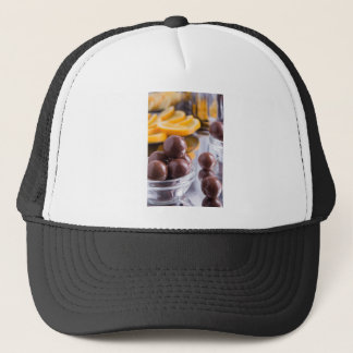 Chocolate candies in a small glass bowl close-up trucker hat