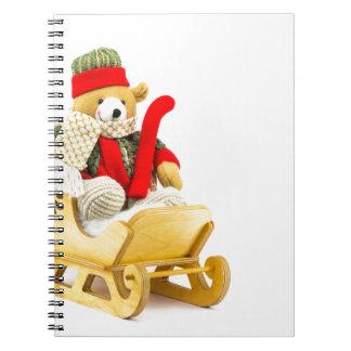 Christmas bear in wooden sleigh on white notebook