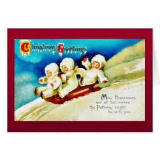 Christmas greeting with three kids snow slading greeting card