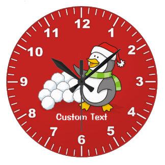Christmas penguin with snow balls waving large clock