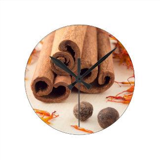 Cinnamon sticks, aromatic saffron and pimento round clock