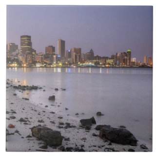 City lights at twilight with debris strewn beach ceramic tile