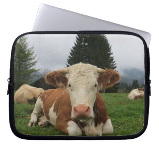 Close up of a brown and white cow laying down laptop sleeve