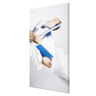Close-up of a person's leg breaking a tile stretched canvas print