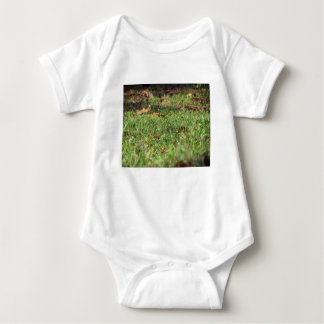 Close up of green grass field and autumn leaves baby bodysuit