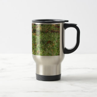 Close up of green grass field and autumn leaves travel mug