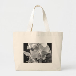 Close up of orchid blossoms in gray scale large tote bag