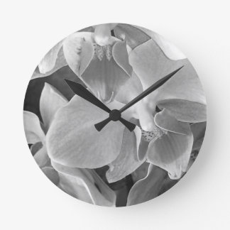 Close up of orchid blossoms in gray scale round clock