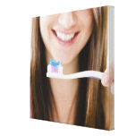 Close-up of smiling young woman holding canvas print