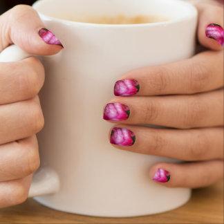 Close-up print of pink rose on women's nail art. minx nail art